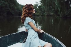 Quite contemplation. Beautiful young woman in elegant dress looking away while sitting in the boat stock images
