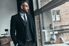 Quite contemplation. Thoughtful man in full suit looking away through the window while standing indoors stock photos