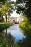 Quite life. The water of a calm river passing near the houses in a peaceful italian morning Stock Photography