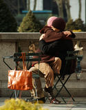 Quite Moment in the Park. A couple enjoys an unusually warm winter day in the park.  She is sitting in his lap and they are quietly, motionlessly hugging Stock Photos