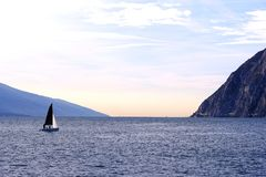 Yachting somewhere in mountains. Quite peaceful photo of a yacht sailing somewhere near mountains. Wonderful natural view, dark deep blue water with light waves stock photo