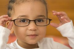 Quite Studious 2. A beautiful young mixed race girl wearing slightly oversized glasses Royalty Free Stock Image