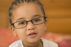 Quite Studious 3. A beautiful young mixed race girl wearing slightly oversized glasses stock photo