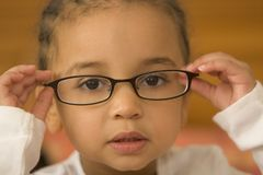 Quite Studious 5. A beautiful young mixed race girl wearing slightly oversized glasses royalty free stock photography