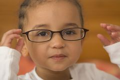 Quite Studious. A beautiful young mixed race girl wearing oversized glasses stock image