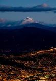 Quito alla notte con la montagna del cotopaxi Immagine Stock