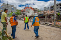Quito, Ecuador - abril, 17, 2016: Casa destruida por terremoto con los salvadores y la maquinaria pesada en la parte del sur de Foto de archivo