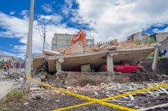 Quito, Ecuador - abril, 17, 2016: Casa destruida por terremoto con los salvadores y la maquinaria pesada en la parte del sur de Foto de archivo libre de regalías
