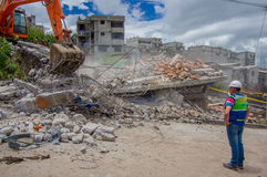 Quito, Ecuador - abril, 17, 2016: Casa destruida por terremoto con los salvadores y la maquinaria pesada en la parte del sur de Imágenes de archivo libres de regalías