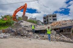 Quito, Ecuador - abril, 17, 2016: Casa destruida por terremoto con los salvadores y la maquinaria pesada en la parte del sur de Fotografía de archivo libre de regalías
