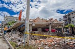 Quito, Ecuador - abril, 17, 2016: Grupo de personas no identificado que mira la casa destruida por terremoto, y maquinaria pesada Imágenes de archivo libres de regalías