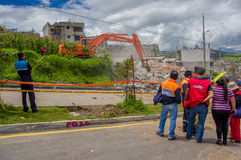 Quito, Ecuador - abril, 17, 2016: Grupo de personas no identificado que mira la casa destruida por terremoto, y maquinaria pesada Foto de archivo libre de regalías