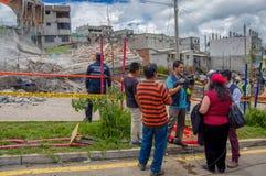 Quito, Ecuador - abril, 17, 2016: Grupo de personas no identificado que mira la casa destruida por terremoto, y maquinaria pesada Imagen de archivo libre de regalías