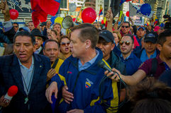 Quito, Ecuador - April 7, 2016: Closeup opposition leader Andres Paez surrounded by people, police and journalists Royalty Free Stock Photos