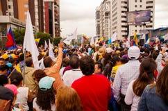 Quito, Ecuador - April 7, 2016: Menigte van niet geïdentificeerde mensen met Ecuatoriaan en witte vlaggen ondersteunend president Stock Foto's