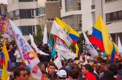 Quito, Ecuador - April 7, 2016: Menigte van niet geïdentificeerde mensen met Ecuatoriaan en witte vlaggen ondersteunend president Stock Foto