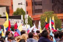 Quito, Ecuador - April 7, 2016: Menigte van niet geïdentificeerde mensen met Ecuatoriaan en witte vlaggen ondersteunend president Stock Afbeelding