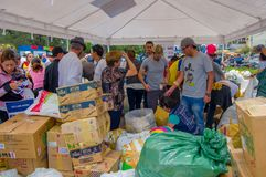 Quito, Ecuador - April, 17, 2016: Nicht identifizierte Leute in Quito, das Katastrophenhilfelebensmittel, Kleidung, Medizin berei Lizenzfreies Stockfoto