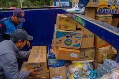 Quito, Ecuador - April, 17, 2016: Nicht identifizierte Leute, die Katastrophenhilfelebensmittel, -kleidung, -medizin und -wasser  Stockfotos