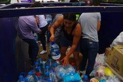 Quito Ecuador - April, 17, 2016: Oidentifierat folk på en bil som ger vatten för jordskalvöverlevande i kusten Arkivfoto