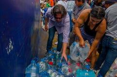 Quito Ecuador - April, 17, 2016: Oidentifierat folk på en bil som ger vatten för jordskalvöverlevande i kusten Royaltyfri Foto