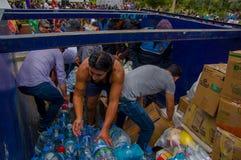 Quito Ecuador - April, 17, 2016: Oidentifierat folk på en bil som ger vatten för jordskalvöverlevande i kusten Royaltyfri Fotografi