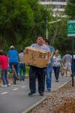 Quito, Ecuador - April, 17, 2016: Tragendes Lebensmittel, Kleidung, Medizin und Wasser der nicht identifizierten Leute für Erdbeb Lizenzfreie Stockbilder