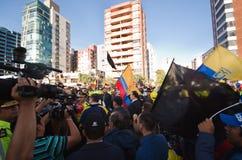 Quito, Ecuador - 7 aprile 2016: Gruppo di persone che iscenano i segni di protesta, i palloni con la polizia ed i giornalisti dur Immagine Stock