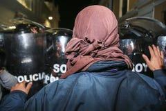 Quito, Ecuador - 27. August 2015: Bemannen Sie tragende Denimjacke und Gesicht umfasste Stellung vor dem Polizeischildprotest Lizenzfreies Stockbild