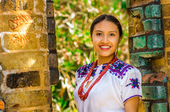 QUITO, ECUADOR - AUGUST, 30 2017: Portrait of a young indigenous woman wearing a typical andean clothes, posing for. Camera in front of an old wall, in the park Stock Photography
