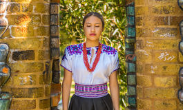 QUITO, ECUADOR - AUGUST, 30 2017: Portrait of a young indigenous woman wearing a typical andean clothes, posing for. Camera in front of an old wall, in the park Royalty Free Stock Photos