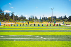 QUITO, ECUADOR - 8 AUGUST, 2016: Row of people stretching seated on football field located in inner city park La Carolina, artific Royalty Free Stock Photo