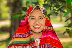 QUITO, ECUADOR - AUGUST, 30 2017: Unidentified young indigenous woman wearing a typical andean clothes, covering her. Head with a colorful blanket in the park Royalty Free Stock Photography