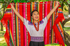 QUITO, ECUADOR - AUGUST, 30 2017: Unidentified young indigenous woman wearing a typical andean clothes, holding with. Both hands a colorful blanket in the park Royalty Free Stock Image