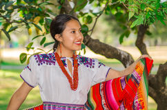 QUITO, ECUADOR - AUGUST, 30 2017: Unidentified young indigenous woman wearing a typical andean clothes, holding in her. Hand a colorful blanket in the park Royalty Free Stock Photos