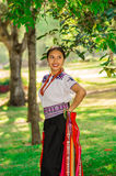 QUITO, ECUADOR - AUGUST, 30 2017: Unidentified young indigenous woman wearing a typical andean clothes, holding in her. Hand a colorful blanket in the park Stock Photos