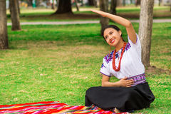QUITO, ECUADOR - AUGUST, 30 2017: Unidentified young indigenous woman wearing a typical andean clothes, sitting in the. Ground doing exercise in the park Stock Photography