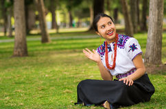 QUITO, ECUADOR - AUGUST, 30 2017: Unidentified young indigenous woman wearing a typical andean clothes, sitting in the. Ground in the park Royalty Free Stock Photos