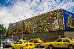 QUITO ECUADOR AUGUSTI 20 2017: Härliga vägg- grafitti på en vägg med några bilar som parkeras i den centrala Quito, Ecuador Fotografering för Bildbyråer