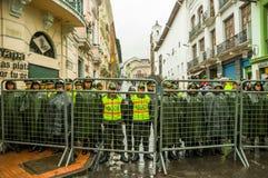 Quito, Ecuador - Augustus 27, 2015: De politieagenten achter metaal schermen barrricade het wachten van op orden tijdens massadem Royalty-vrije Stock Afbeelding