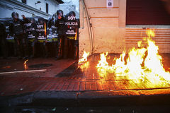 Quito, Ecuador - Augustus 27, 2015: De stoep op brand tijdens hevige protesten, grote groep relpolitie wacht op Royalty-vrije Stock Afbeeldingen