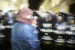 Quito, Ecuador - Augustus 27, 2015: Mens denimjasje dragen en behandeld gezicht die status voor politieschilden het protesteren Stock Afbeelding