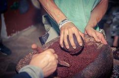 Quito, Ecuador, 30 Augustus, 2017: Mensen die een cacaobonen over een rots, naast een houten fornuis malen Stock Afbeeldingen