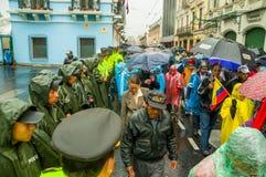 Quito, Ecuador - Augustus 27, 2015: Protesteerders die door stadsstraten lopen met paraplu's die rij van politieagenten overgaan Royalty-vrije Stock Foto's