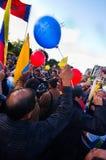 Quito, Ecuador - 7 de abril de 2016: Grupo de personas que detiene muestras de la protesta, los globos con policía y a los period Fotografía de archivo