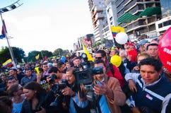 Quito, Ecuador - 7 de abril de 2016: Grupo de personas que detiene muestras de la protesta, los globos con policía y a los period Imagen de archivo libre de regalías