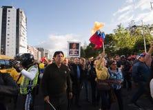 Quito, Ecuador - 7 de abril de 2016: Grupo de personas que detiene muestras de la protesta, los globos con policía y a los period Imágenes de archivo libres de regalías