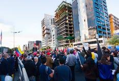 Quito, Ecuador - 7 de abril de 2016: Grupo de personas que detiene muestras de la protesta, los globos con policía y a los period Foto de archivo