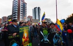 Quito, Ecuador - 7 de abril de 2016: Grupo de personas que detiene muestras de la protesta, los globos con policía y a los period Imagenes de archivo