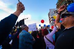 Quito, Ecuador - 7 de abril de 2016: Grupo de personas que detiene muestras de la protesta, los globos con policía y a los period Fotos de archivo